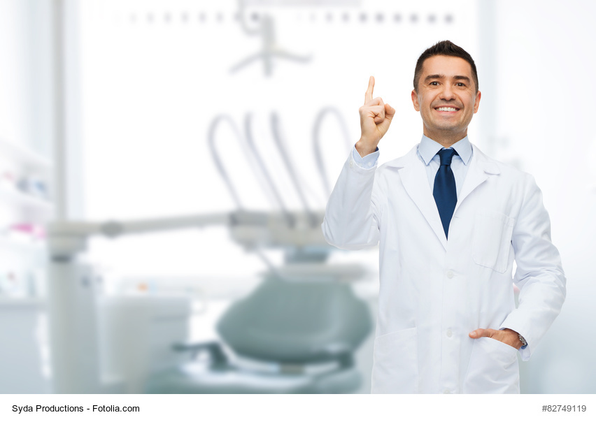 smiling male dentist pointing finger up