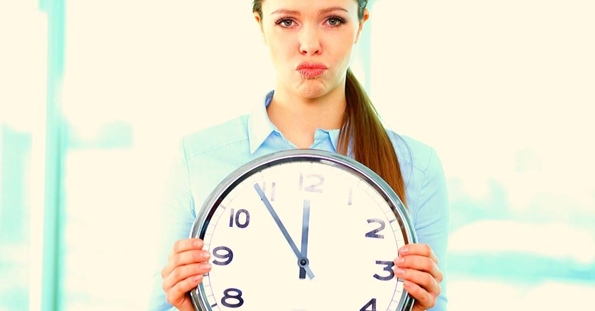 Frau mit Uhr - Kurzarbeit in der Zahnarztpraxis